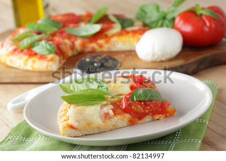 Wedge of Margherita pizza with mozzarella, tomato, and basil