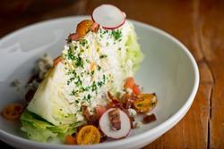 Wedge salad. Classic American salad with iceberg lettuce, blue cheese dressing, red onions, bacon lardons, Parmesan cheese, olive oil, lemon juice, salt and pepper. A Fine dining restaurant classic.