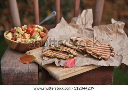 Wedges of quesadilla on a cutting board with bowl of corn salsa
