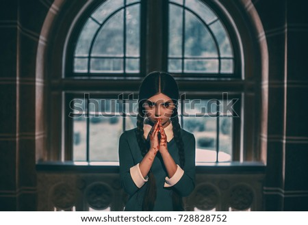 Wednesday Addams. Angry girl student after the exam with bloody hands. Gothic look for a Halloween party.Creative colors.The background of the old castle window #728828752