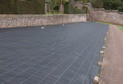 Weed Suppressant Fabric Covering a Bed in a Walled Organic Vegetable Garden in Rural Devon, England, UK
