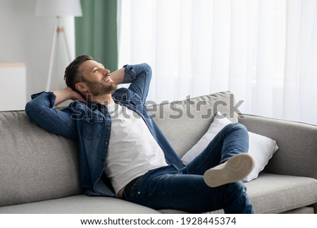 Weekend at home. Relaxed middle-aged bearded man in casual resting at home, holding hands behind head and smiling while reclining on sofa, looking at copy space, living room interior ストックフォト ©