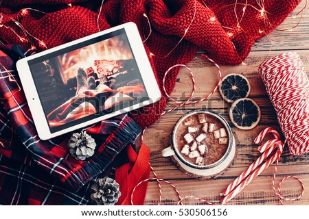 Weekend homely scene. Warm knit sweater and cup of hot cocoa with marshmallows. Christmas lollipop, led lights string and other holiday decor. Tablet pc with film, watching winter movies.