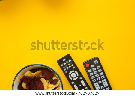 Weekend, leisure and hobby concept. a bright one-colore yellow background with a bowl with potato and beetroot chips and remote controls. Space for your text or product display #782937829
