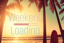 Weekend loading words on surfboard and palm tree on tropical sunset beach abstract background. Summer vacation and sport extreme concept. Vintage tone filter color style.