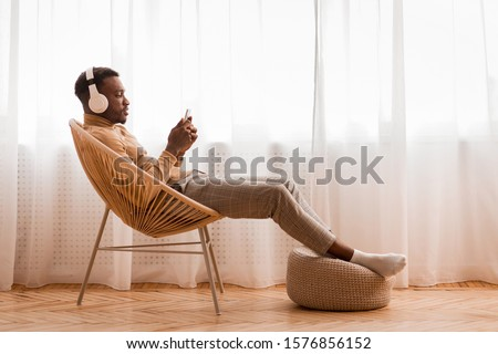 Weekend. Relaxed Black Man In Wireless Headset Using Mobile Phone Listening To Audiobook Sitting On Modern Chair Against Window Indoor Stockfoto ©