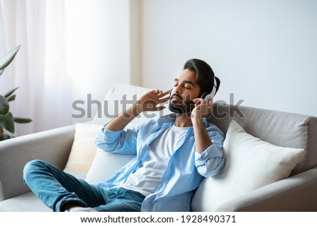 Weekend Rest. Young arab guy in wireless headphones listening audiobook at home, calm eastern man sitting with closed eyes on couch in living room, enjoying domestic leisure, free space Photo stock ©