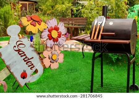Weekend Summer Backyard Party Or Picnic Concept. Sign Garden Close-up. BBQ Grill With Tools, Outdoor Wood Furniture Plants And House On The Blurred Background