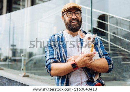 Weekend walk. Dark-haired man laughing out loud while enjoying weekend walk with little white dog