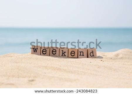 Weekend word on wood rubber stamps stack on the sand beach for vacation and summer season concept, beautiful ocean view during daytime on a sunny day with blue sky on background
