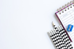 Weekly organizer planner, shaper and sharp pencil surrounded by dull pencils. Stationery flat lay. Back to school. White background. Business, sharp idear concept. Mock up