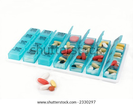Weekly pill organizer containing a variety of pills and vitamins