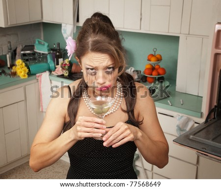 Weeping Caucasian woman drinks a martini in her messy kitchen