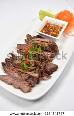 Weeping Tiger Sirloin Steak, In Thai 'Suea Rong Hai' is a Thai marinated beef. Marinade the sirloin steak with fish sauce, soy sauce, sugar, garlic, ground coriander seed, and black pepper Stock photo ©