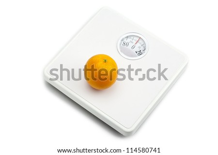 Weighing scale and orange fruit on white