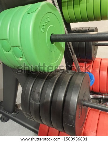 Weight display for weight training in gym. Various sizes of color weights.