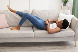 Weight Gain. Black Woman Struggling Zipping Too Small Skinny Jeans Lying On Sofa At Home. Gaining Excess Kilograms, Fat Belly And Visceral Fat Problem Concept