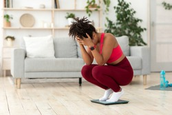 Weight Gain. Desperate Black Girl Crying Standing On Weight-Scales Slimming, Not Losing Weight On A Diet At Home. Copy Space