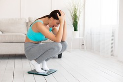 Weight Gain. Unhappy Woman Crying Standing On Weight-Scales Not Losing Weight On Diet Slimming At Home. Free Space