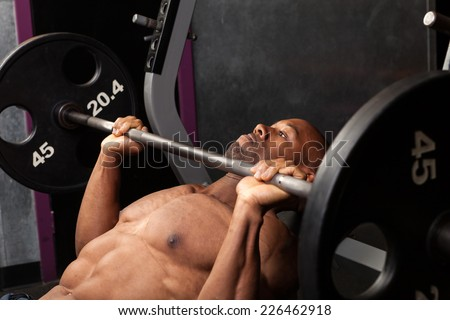 Weight lifter at the bench press lifting a barbell on an