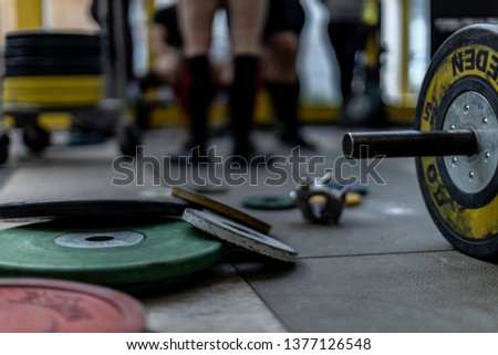 weight lifting bar and weights on the ground of a gym
