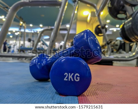 Weight loss and getting ripped and fit at a modern and well equipped gym with closeup of two small blue dumbbells of 2 kg for a healthier New Year resolution