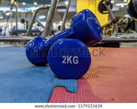 Weight loss and getting ripped and fit at a modern and well equipped gym with closeup of two small blue dumbbells of 2 kg