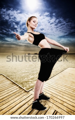 Weight loss and healthy lifestyle. Happy woman fitness girl showing how much weight she lost, giving thumb up success hand sign. Outdoor. Beach pier