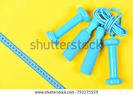 Weight loss and sports concept. Gym and healthy lifestyle tools. Centimeter in blue color near sport equipment. Dumbbells and measuring tape lay top on yellow background. #792171559