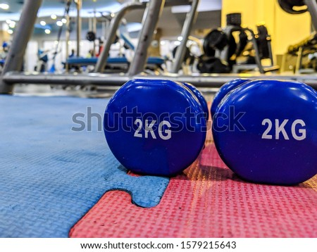 Weight loss and strength increase in gym with a closeup of two blue 2 kg small dumbbells in a cool and modern well equipped gym