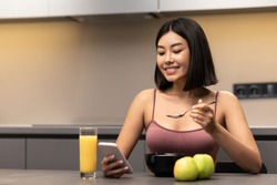 Weight Loss Application. Slim Korean Woman Using Phone Eating Oatmeal Porridge For Breakfast Sitting At Table In Modern Kitchen Indoor. Healthy Diet, Nutrition, Dieting For Slimming. Free Space