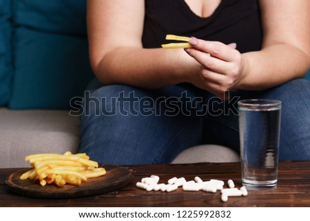 weight loss, atherosclerosis, diabetes, medical therapy and treatment. overweight woman glutton eating junk food taking lot of pills
