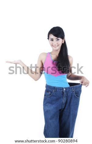 Weight loss concept: Beautiful Asian woman showing her old jeans