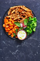 Weight loss diet: grilled chicken breast and veggies of sweet potato,  boiled broccoli on a black plate on a dark concrete background with sour cream, radish and spinach, top view, close-up
