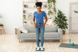 Weight-Loss Motivation. Smiling African Woman Weighing Herself After Successful Slimming And Weight Loss Standing On Scales Posing At Home. Full Length, Free Space For Text