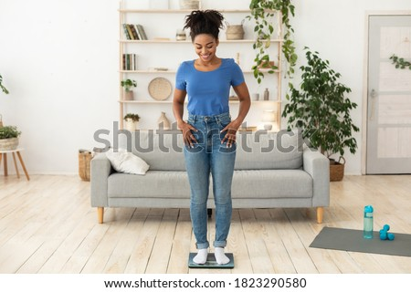 Weight-Loss Motivation. Smiling African Woman Weighing Herself After Successful Slimming And Weight Loss Standing On Scales Posing At Home. Full Length, Free Space For Text Photo stock ©