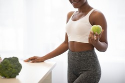 Weight Loss Nutrition. Unrecognizable African Fitness Lady Posing With Apple Standing In Kitchen Indoors, Cropped. Healthy Diet For Slimming. Cooking For Weight-Loss Concept