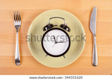 weight loss or diet concept. stock image of alarm clock on plate #344331620