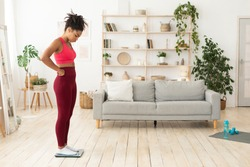 Weight-Loss Problem. Frustrated Black Girl Standing On Weight-Scales Having A Hard Time Slimming, Gaining And Not Losing Excess Weight, Fighting Obesity At Home. Free Space For Text, Full-Length