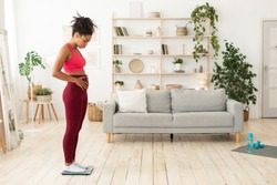 Weight Loss Problem. Unhappy African American Woman Standing On Weight-Scales Touching Fat Belly At Home. Not Losing Excess Weight, Fighting Obesity Concept. Copy Space For Text, Full-Length