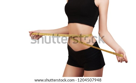 Weight loss, slim body, healthy lifestyle concept. Fitness girl measuring her waistline with measure tape, isolated on white. Copy space. Slim woman measuring her waist Сток-фото ©