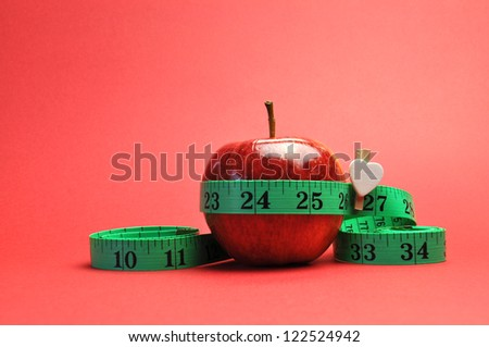 Weight loss slimming diet concept, New Year Resolution, with green measuring tape around a bright red apple, set against a red background.