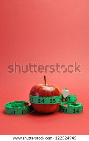 Weight loss slimming diet concept, New Year Resolution, with green measuring tape around a bright red apple, set against a red background. (vertical portrait orientation)