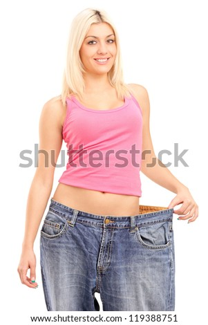 Weight loss woman with old pair of jeans isolated on white background