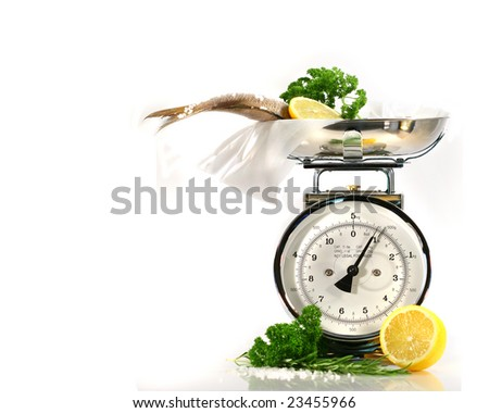 Weight scale, fish,lemon on parchment paper against white background