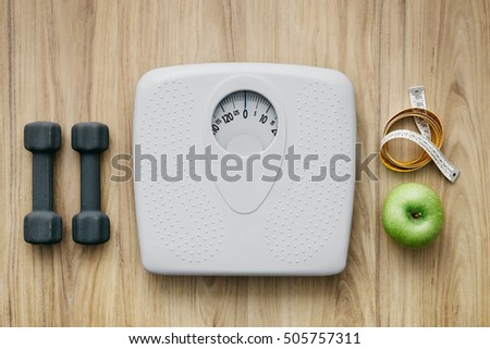 Weight scale, healthy snack, measuring tape and dumbbells on a table, weight loss and sports concept, flat lay