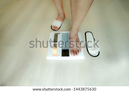 weight scale is weighed by man feet who wear white japan slipper standing to measure his weight in lose weight concept