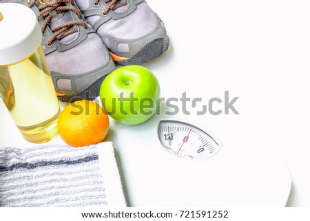 Weight scales, sneakers, handkerchief,water bottle and fruit on white background Selective focus,Conception about health care
