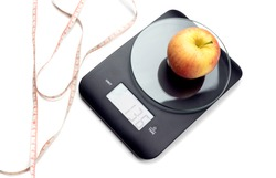Weight tracking concept. The comfortable, contemporary, electronic, black kitchen scale for weighing products, apple and centimeter on a white background close-up