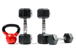 Weight training equipment. Big red kettlebell, dumbells. Isolated on white.